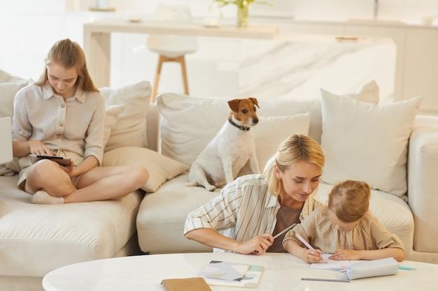 Scène de famille de jeune mère aidant la petite fille à dessiner ou étudier avec une adolescente et un chien assis sur un confortable canapé blanc à l'intérieur de la maison
