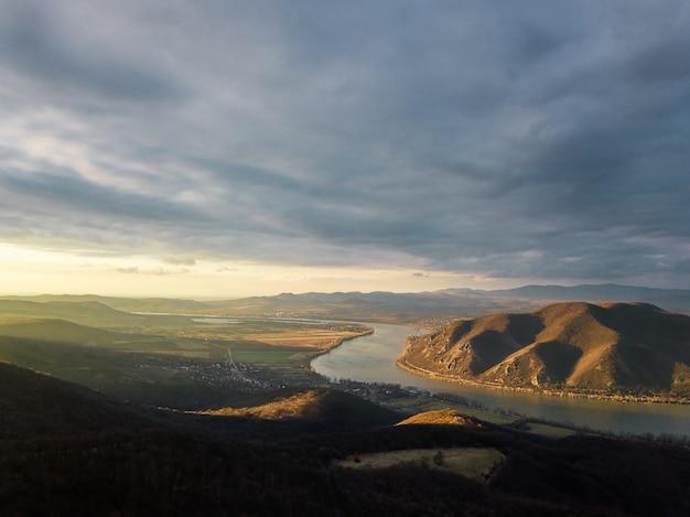 Scène fascinante d'une rivière entre forêt et colline sous le ciel nuageux