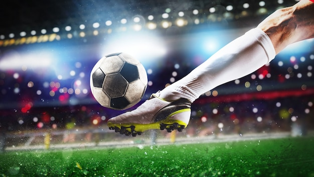 Scène de football au match de nuit avec gros plan d'une chaussure de football frappant la balle avec puissance