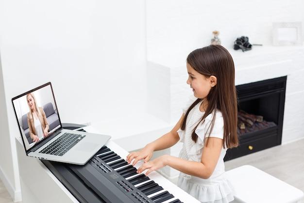 Scène de formation en ligne de cours de piano ou d'apprentissage en classe électronique pendant la propagation du coronavirus ou la situation de crise de covid-19, un vlog ou un enseignant fait un cours de piano en ligne pour enseigner aux élèves que les élèves apprennent de chez eux.