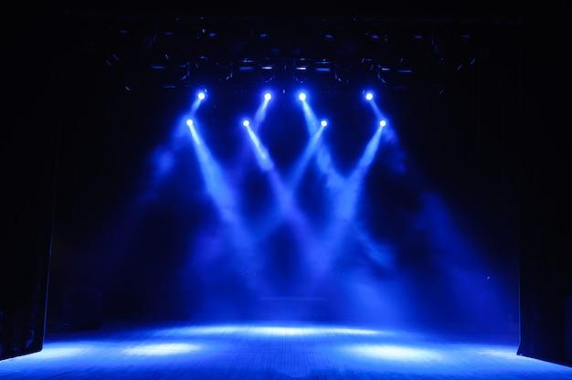 Scène libre avec lumières, fond de scène vide, projecteur, néon, fumée.