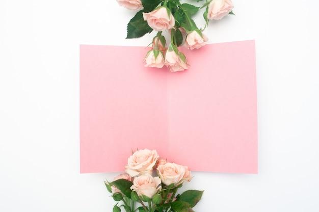 Scène de maquette de mariage ou d'anniversaire. feuille de papier ouverte vierge avec place pour le texte de la carte de voeux. bouquet de roses roses.