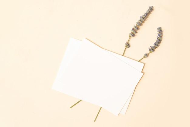 Scène de maquette de papeterie d'été. carte de visite vierge avec des fleurs de lavande sur fond de table texturé beige. mise à plat, vue de dessus