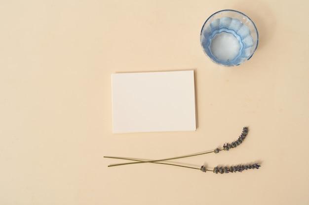 Scène de maquette de papeterie d'été. carte de visite vierge avec des fleurs de lavande et un verre d'eau sur fond de table texturé beige. mise à plat, vue de dessus