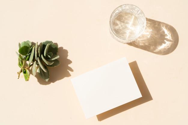 Scène de maquette de papeterie d'été. carte de visite vierge et verre d'eau claire sur fond de table texturé beige