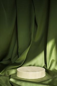 Scène minimale abstraite avec podium cylindrique de forme géométrique sur surface verte
