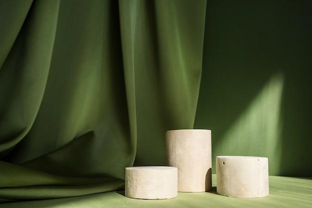 Scène minimale abstraite avec des podiums cylindriques de formes géométriques sur une surface verte