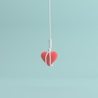 Scène minimale de corde suspendue autour du cœur rouge.