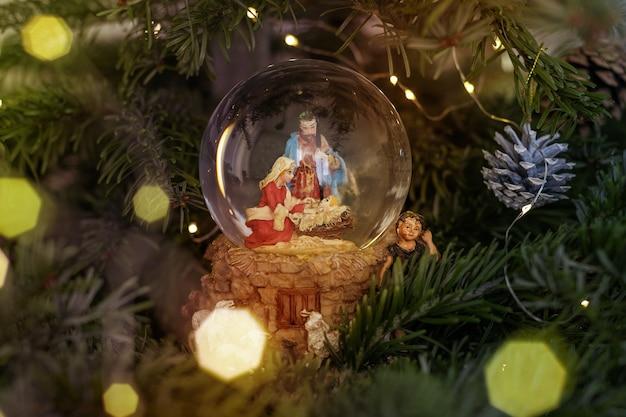 Scène de la nativité de jésus-christ dans une boule de verre sur un arbre de noël