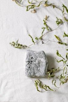 Scène naturelle abstraite avec pierre géométrique comme podium ou piédestal pour présentation de produits ou expositions sur textile blanc avec décor de branche. scène pour montrer tous les produits pour la publicité. mise à plat