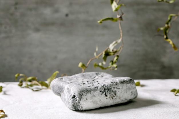 Scène naturelle abstraite avec pierre à texture géométrique comme podium ou socles pour présentation de produits ou expositions sur textile blanc avec décor de branche. scène pour montrer tous les produits pour la publicité.
