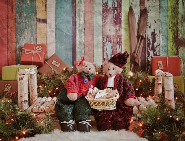 Scène de noël - deux ours en peluche sur un banc en bois en cadeaux nouvel an et la lumière