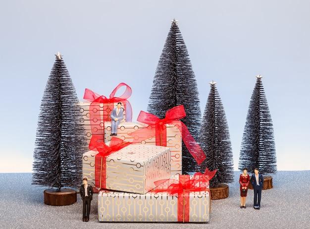 Scène de noël avec des sapins miniatures, des personnes et des cadeaux décorés