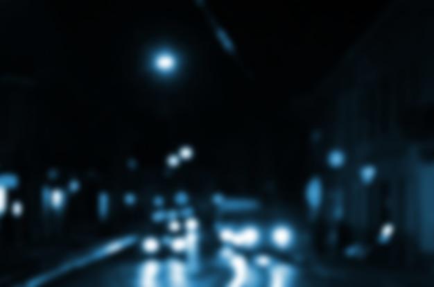 Scène de nuit floue de la circulation sur la chaussée. image défocalisée de voitures voyageant avec des phares lumineux.