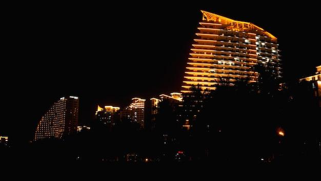 La scène de nuit noire d'un immeuble de bureaux ou d'un hôtel avec des lumières