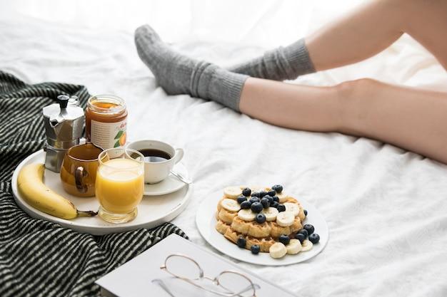 Scène de petit déjeuner confortable au lit un week-end avec du café et des gaufres