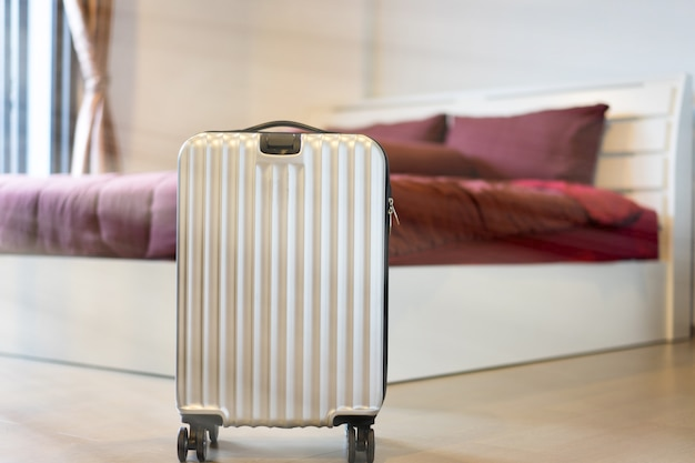 Une scène de prêt à la caisse avec les bagages et le lit dans la chambre d'hôtel.