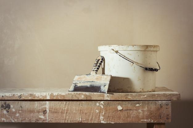Scène de réparation d'appartement. un seau avec du mastic et un couteau à mastic sur un support en bois
