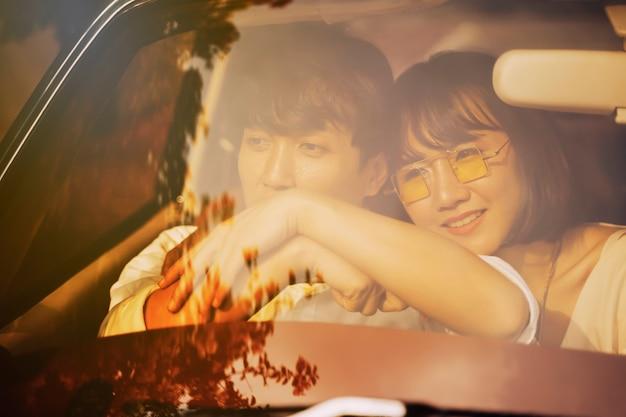 Scène romantique d'amour jeune couple en voiture latérale avec lumière chaude au coucher du soleil.