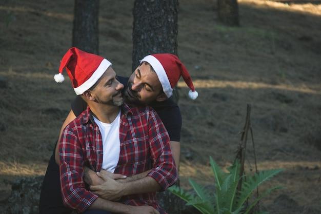 Scène romantique de jeune couple gay avec des chapeaux de noël rouges dans le parc forestier