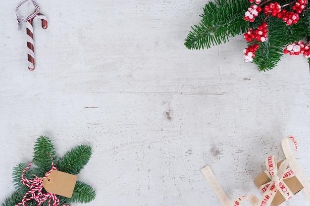 Scène de style plat de noël - cadre avec des brindilles de sapin à feuilles persistantes et une boîte cadeau