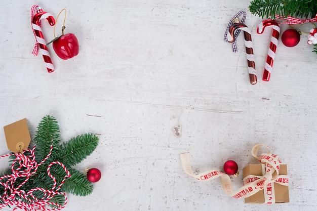 Scène de style plat de noël - cadre avec sapin à feuilles persistantes, décorations et boîte cadeau