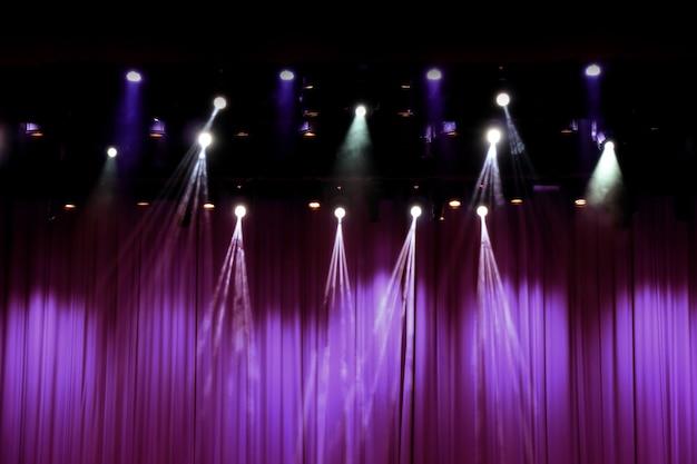 Scène de théâtre avec des rideaux pourpres et des projecteurs.