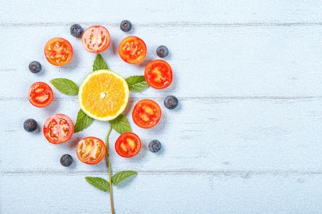 Scène de tomate créative sur une table en bois bleue.