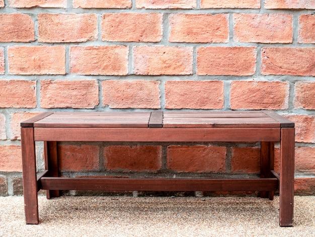 Scène de trottoir avec banc en bois et mur de briques rouges.