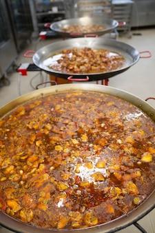 Scènes de vrai travail d'équipe par des professionnels de la haute cuisine gastronomique pour des événements sociaux paella valencia