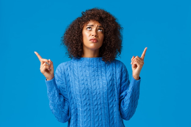 Sceptique et bouleversée, sombre femme afro-américaine timide n'aime pas ce qui se passe, exprime sa désapprobation et sa tristesse, regardant vers le haut jaloux, envie d'un ami acheté qu'elle voulait, bleu