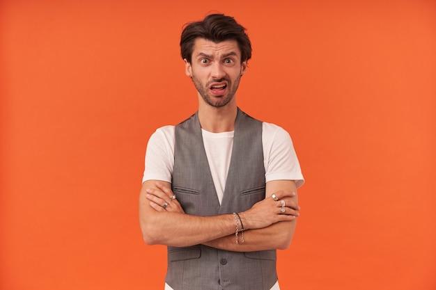 Sceptique jeune homme méfiant avec des poils et un sourcil soulevé des questions ayant une expression sérieuse et perplexe debout avec les bras croisés