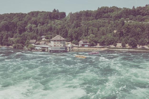 Schaffhouse, suisse - 22 juin 2017 : bateau avec des gens flottant à la cascade les chutes du rhin. c'est l'une des principales attractions touristiques. journée d'été avec ciel bleu