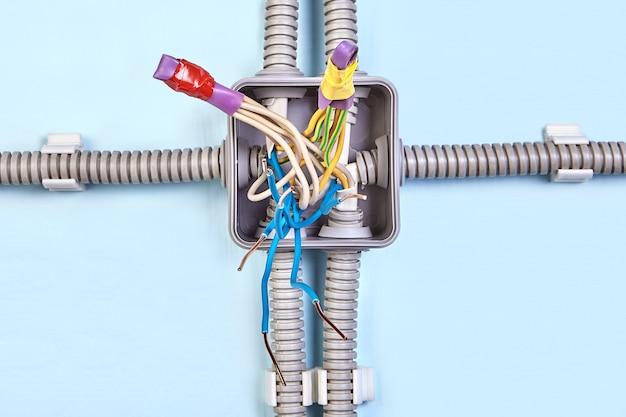 Schéma d'une boîte de jonction avec câblage en cuivre dans une gaine thermorétractable scotchée, gros plan.