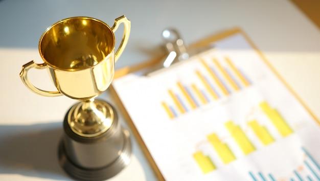 Schéma financier avec trophée en or sur fond. entreprise réussie