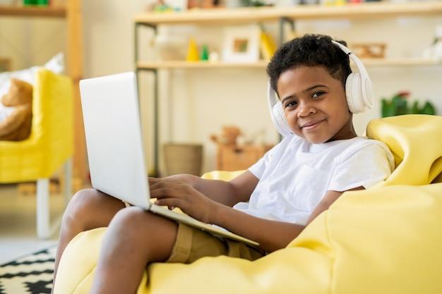 Schoolkid adorable concentré dans des écouteurs regardant l'écran de l'ordinateur portable tout en jouant à un jeu ou en suivant un cours éducatif en ligne