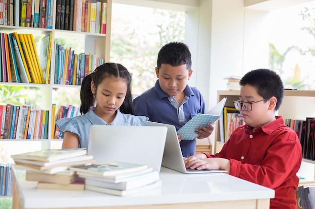 Schoolkid fait ses devoirs à la bibliothèque à l'école. retour à l'école.