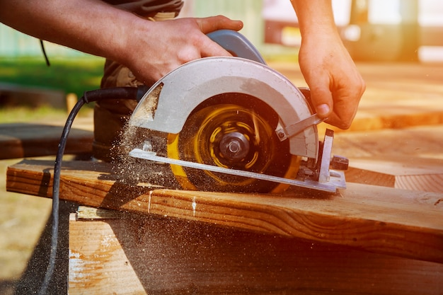 Scie circulaire. charpentier utilisant une scie circulaire pour poutre en bois