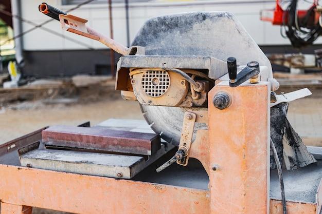 La scie circulaire diamantée coupe des dalles de pavage en béton. gros plan de la machine de découpe de béton.