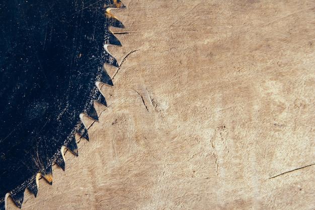 Scie circulaire à lame sur le fond de la table en bois