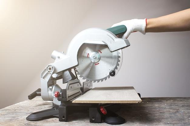 La scie circulaire verte moderne se trouve sur une table en bois. lame de scie circulaire en bois avec insertions en alliage dur.