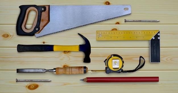 Scie à marteau ruban à mesurer essayez crayon carré et ciseau collection d'outils à main pour le travail du bois sur un établi en bois