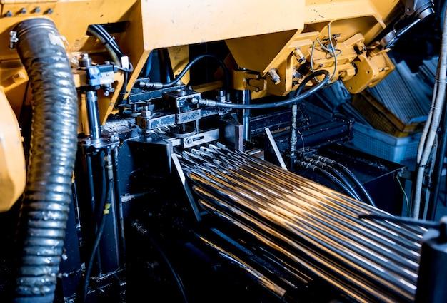 Scie à ruban automatique avec refroidissement par eau pour couper les tuyaux métalliques.