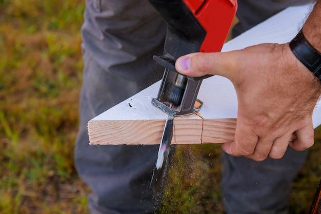 Scie sauteuse à outils de coupe professionnelle, planche de sciage en bois coupée ferme la main du menuisier avec de la sciure de bois.