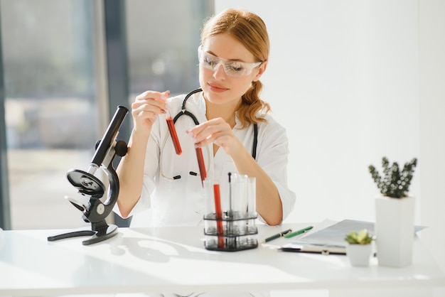 Scientifique à l'aide d'un microscope dans un laboratoire, test de vaccin contre le coronavirus covid19