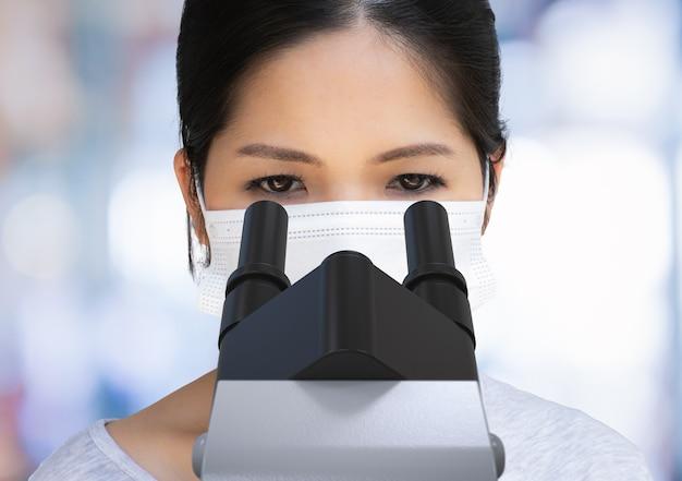 Scientifique asiatique portant un masque facial et regardant un microscope