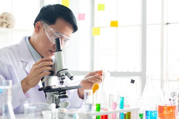 Un scientifique asiatique regarde au microscope en laboratoire.