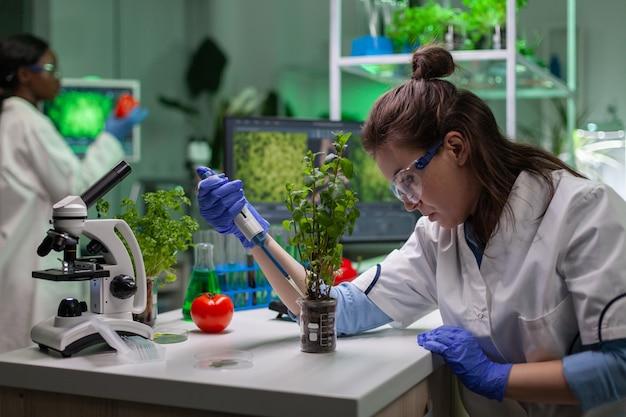 Scientifique de biochimiste prenant le liquide vert avec le puttin de micropieptte sur le jeune arbre