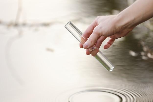Un scientifique et biologiste hydro-biologiste prélève des échantillons d'eau pour analyse à l'extérieur. la main recueille l'eau dans un tube à essai. concept de pollution de l'eau de l'étang.