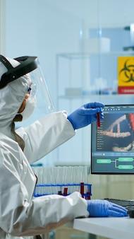 Scientifique en biotechnologie portant un costume ppe faisant des recherches dans un laboratoire équipé. chimistes examinant l'évolution du virus sur pc en utilisant la haute technologie pour la recherche scientifique sur le développement de vaccins contre covid19